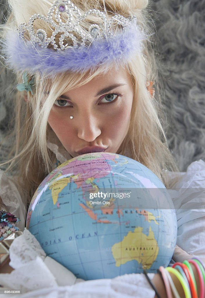 portrait of a funky woman kissing a globe : Stock Photo