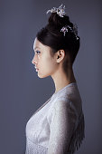 Profile of futuristic young woman. Beautiful young multi-racial asian caucasian model cyber girl in silver urban clothes with conceptual hairstyle and make-up against blue copy-space background. Side
