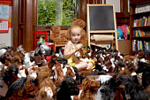 Portrait of a girl among her toy horses