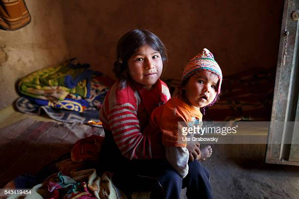 Portrait of a girl and her brother in the Andes of Bolivia on April 16 2016 in Tarwachapi Bolivia