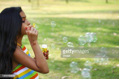 Portrait of a girl blowing soap bubbles : Stock Photo