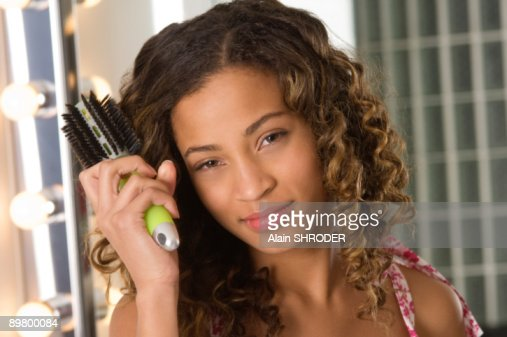 Portrait of a girl brushing her hair : Stock Photo