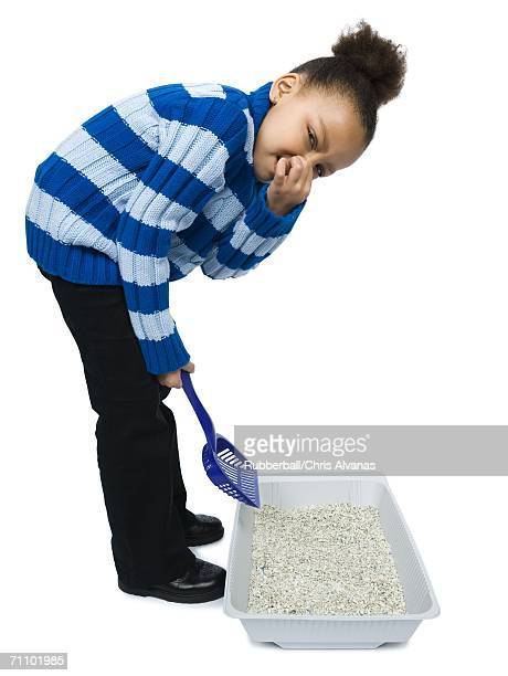 Portrait of a girl cleaning a litter box with a sand pail
