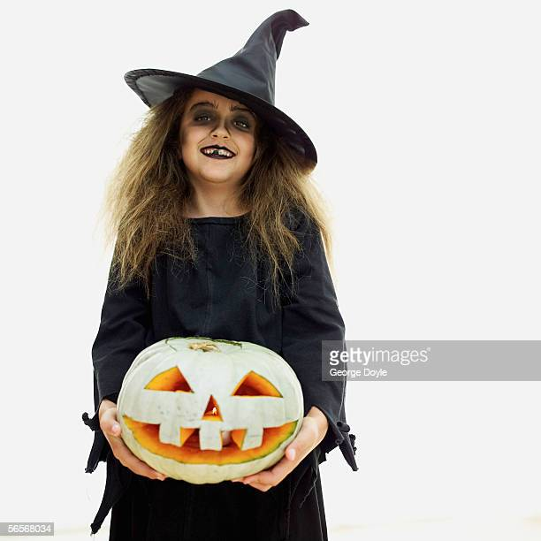 portrait of a girl dressed as a witch holding a carved halloween pumpkin