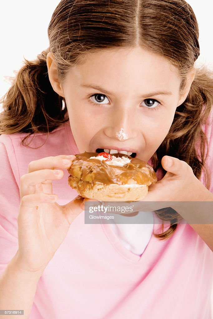 Portrait of a girl eating a donut : Stock Photo
