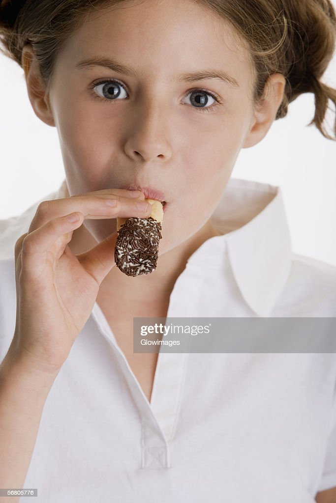 Portrait of a girl eating a pastry : Stock Photo