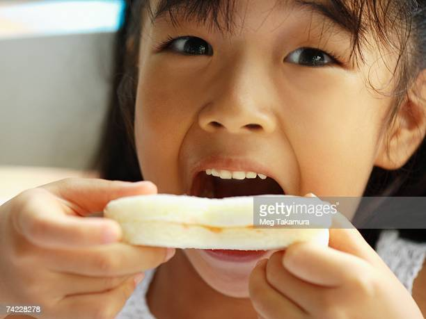 Portrait of a girl eating a slice of bread