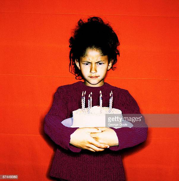 portrait of a girl (8-10) frowning and hugging a birthday cake