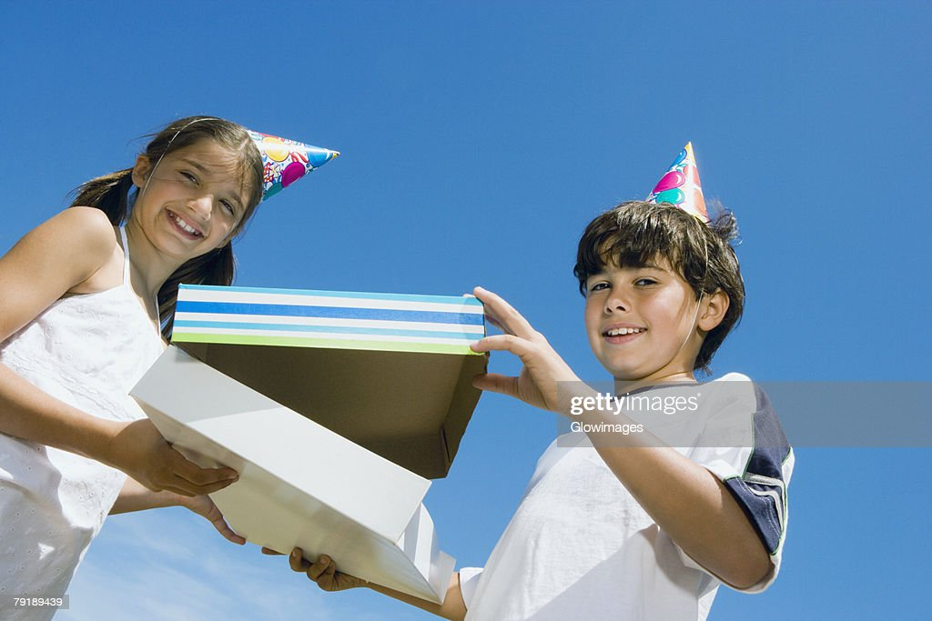 Portrait of a girl giving a birthday present to her brother : Stock Photo