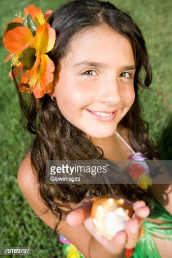 Portrait of a girl holding a conch shell and smiling : Foto de stock