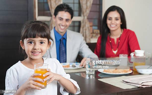 Portrait of a girl holding a glass of juice with her parents in the background