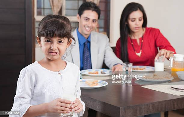 Portrait of a girl holding a glass of milk with her parents in the background