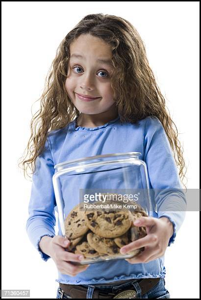 Portrait of a girl holding a jar of cookies
