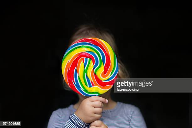 Portrait of a girl holding a multi-colored lollipop