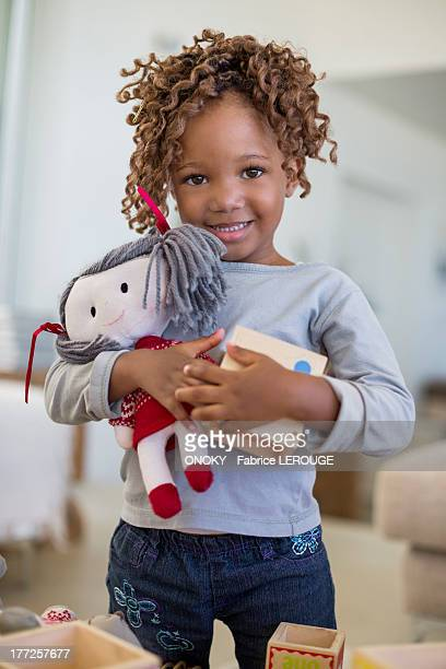 Portrait of a girl holding a rag doll