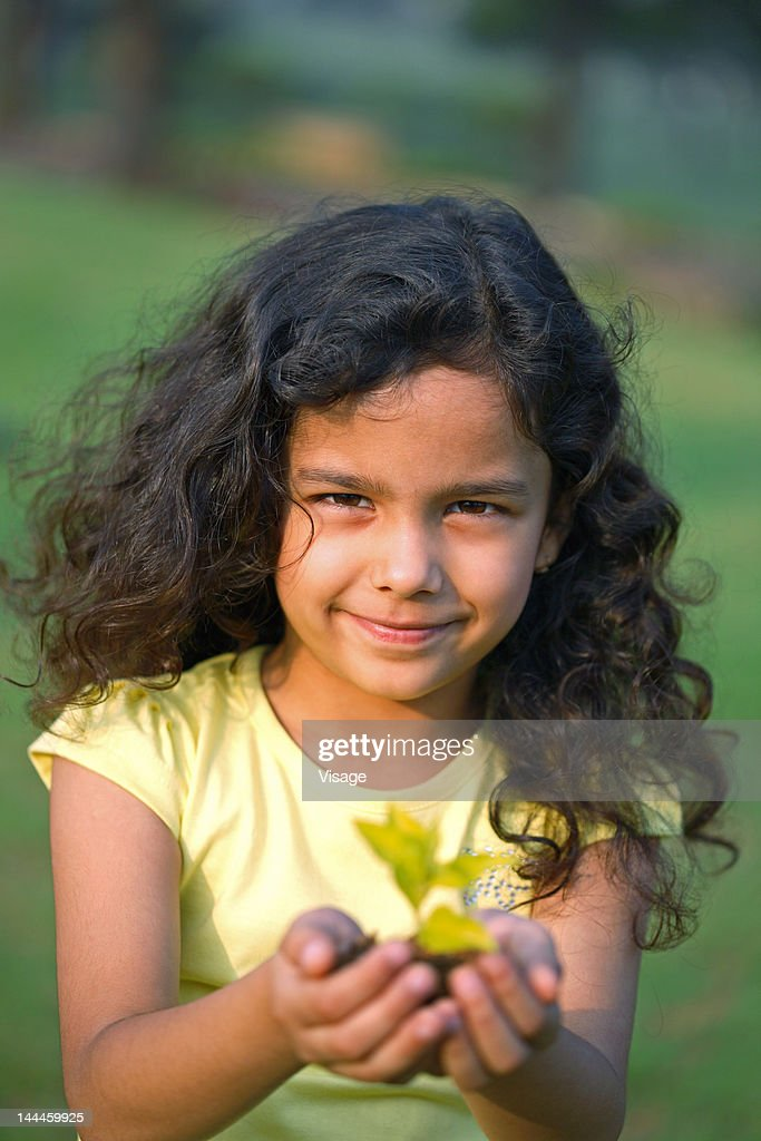 Portrait of a girl holding a sapling : Stock Photo