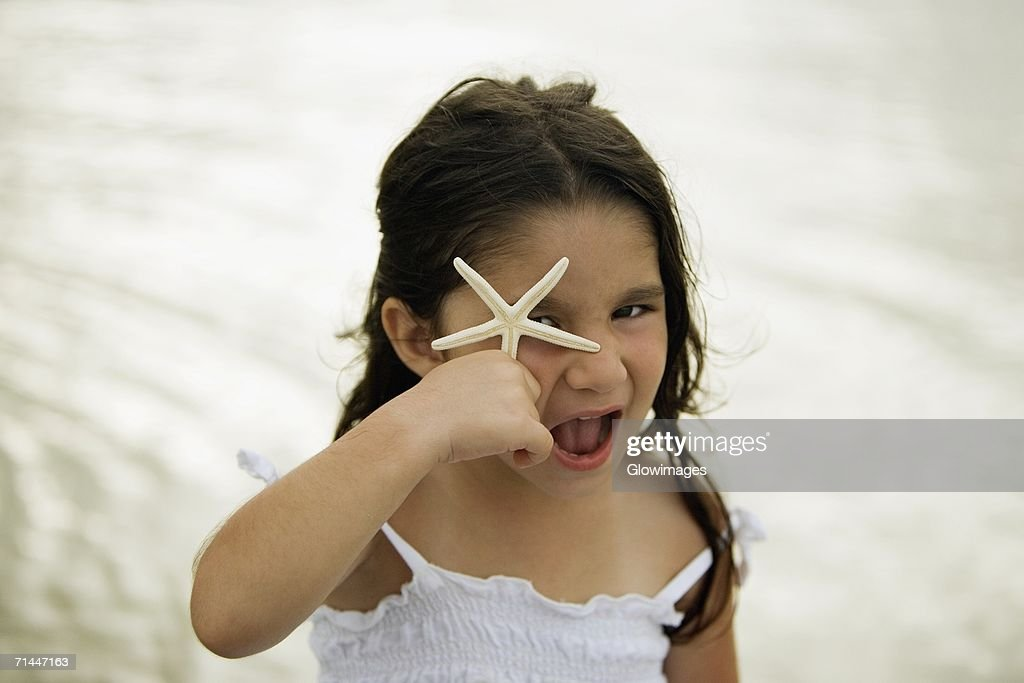 Portrait of a girl holding a star fish in front of her eye : Stock Photo