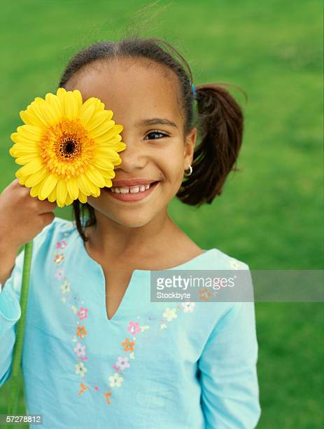 Portrait of a girl holding a sunflower in front of her eye