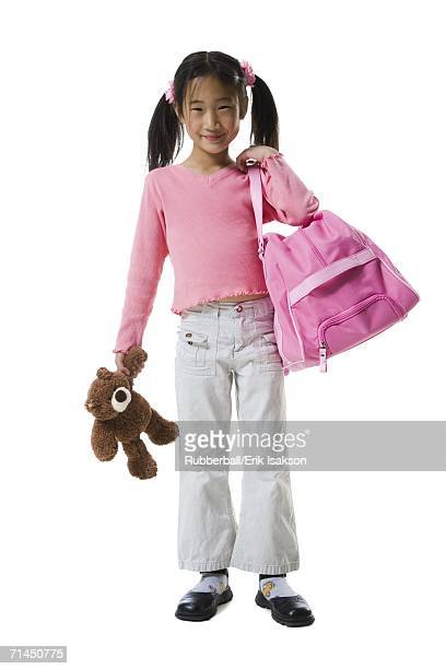 Portrait of a girl holding a teddy bear and a schoolbag