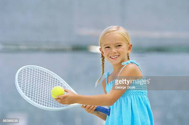 portrait of a girl holding a tennis racket and a tennis ball