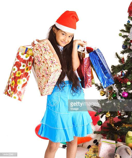 Portrait of a girl holding gifts beside a Christmas tree