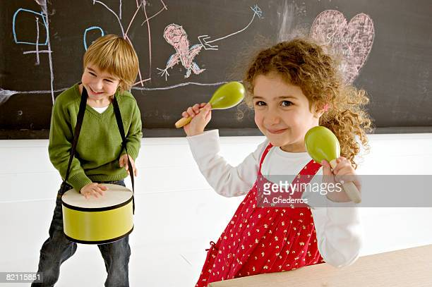 Portrait of a girl holding maracas and her brother playing drum