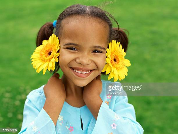 Portrait of a girl holding sunflowers close to her face