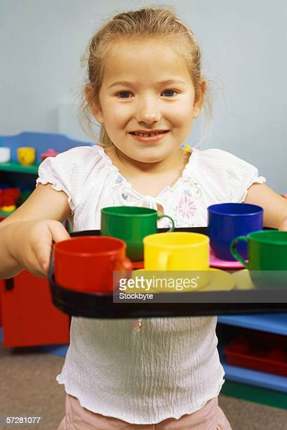 Portrait of a girl holding toy cups on a tray