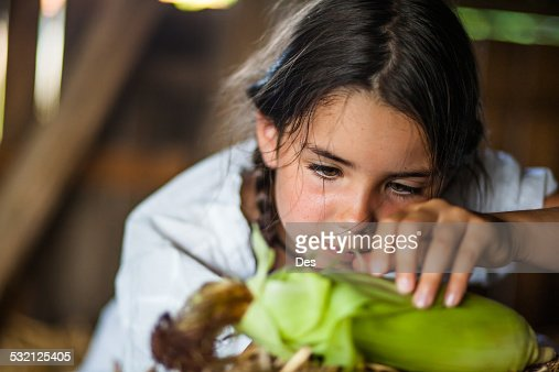 Close-up view of girl (6-7) husking corn