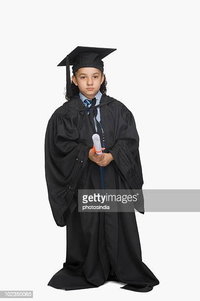 Portrait of a girl in graduation gown holding a diploma