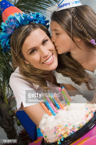 Portrait of a girl kissing her sister in front of a birthday cake : Foto de stock
