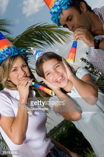 Portrait of a girl laughing with her parents blowing party horn blowers : Stock Photo