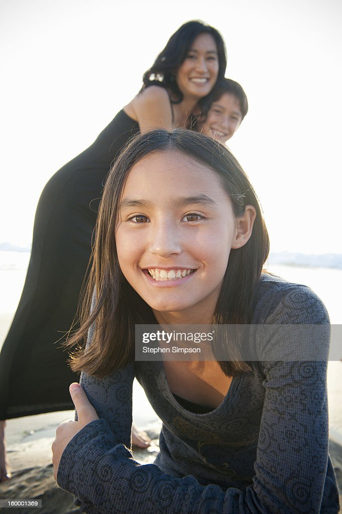 portrait of a girl, mom and brother behind her : Stock Photo