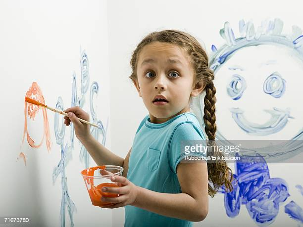Portrait of a girl painting on a wall