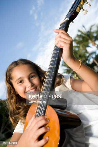Portrait of a girl playing a guitar : Stock Photo