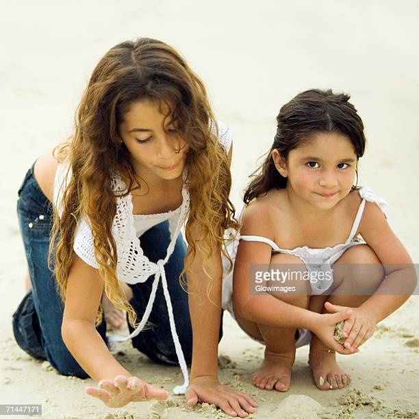 Portrait of a girl playing with her sister on the beach