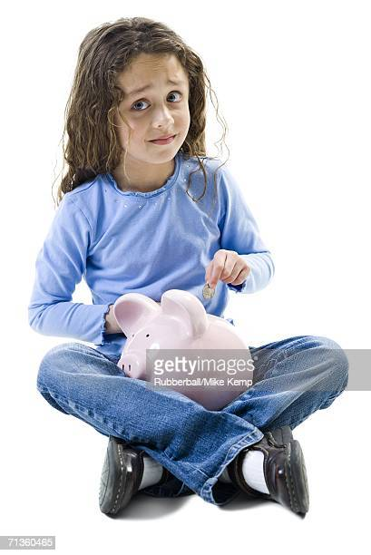 Portrait of a girl putting a coin in a piggy bank