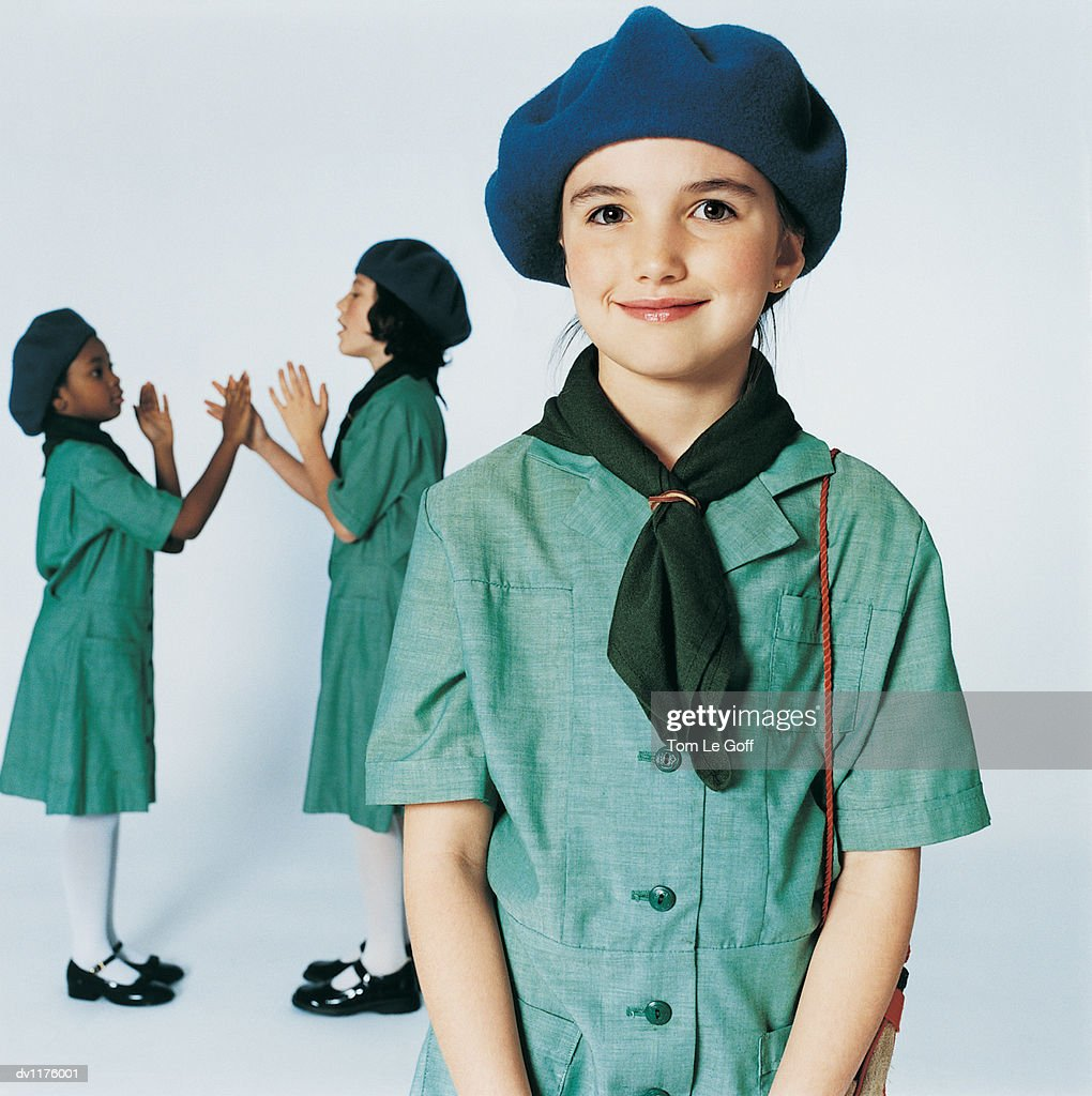 Portrait of a Girl Scout With Two Girl Scouts in the Background Playing Patacake : Stock Photo