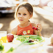 portrait of a girl sitting at a picnic table holding cherries