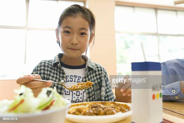 Portrait of a girl sitting at desk for lunch, smiling and looking at camera
