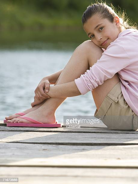 Portrait of a girl sitting on a pier