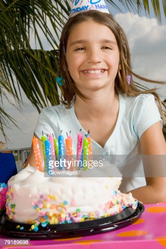 Portrait of a girl smiling in front of a birthday cake : Stock Photo
