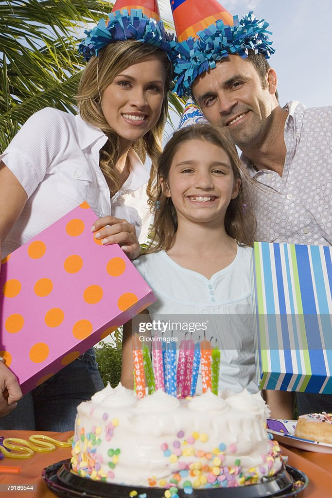 Portrait of a girl smiling with her parents holding birthday presents : Foto de stock