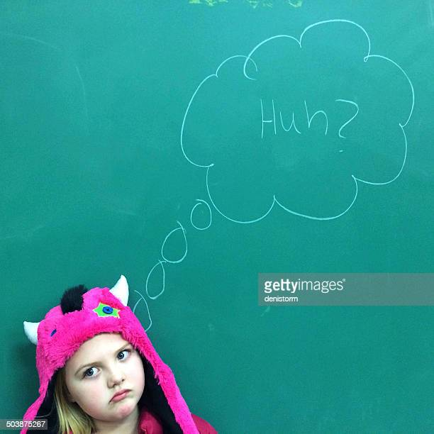 Portrait of a Girl standing in front of blackboard with puzzled expression