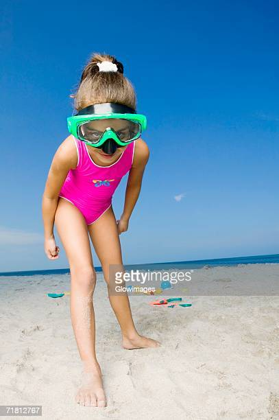 Portrait of a girl standing on the beach and wearing a scuba mask