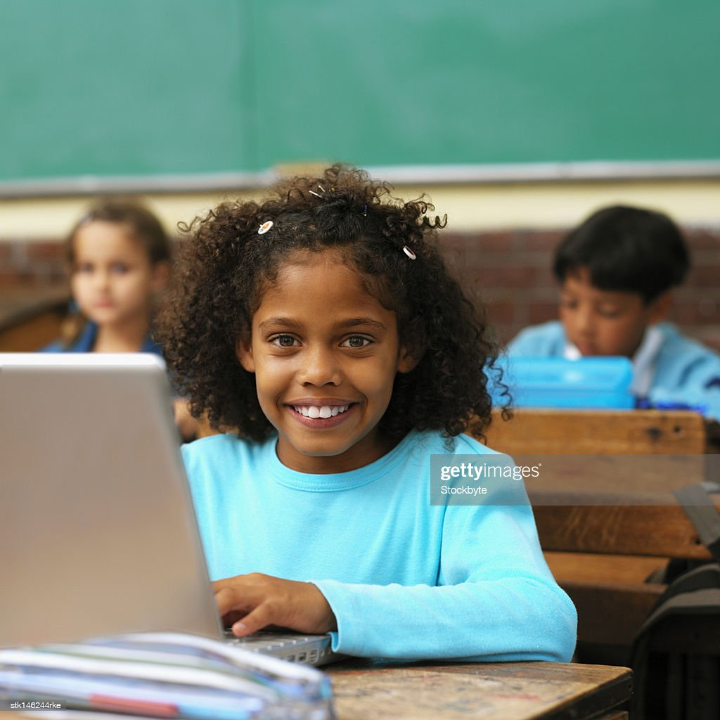 Portrait of a girl using a laptop in a classroom and boy and girl (9-11) in background : Stock Photo