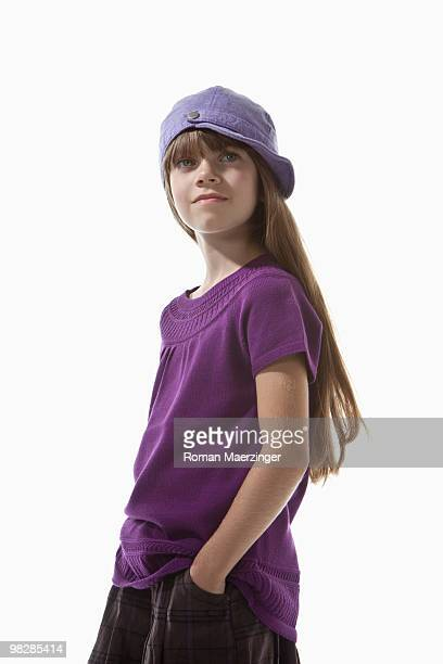 Girl (8-9) with hands in pockets wearing cap