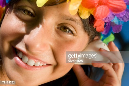 Portrait of a girl wearing flowers and listening to a conch shell : Foto de stock