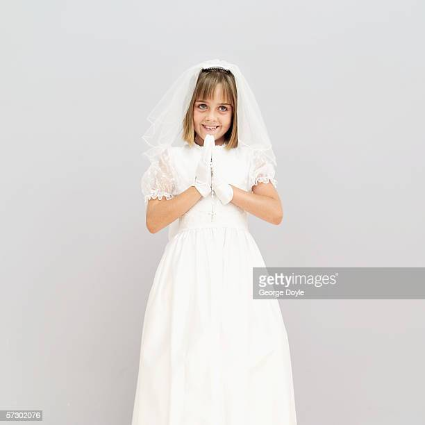 Portrait of a girl (11-13) wearing her first holy communion dress and praying