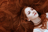 portrait of a girl with beautiful long red shiny hair
